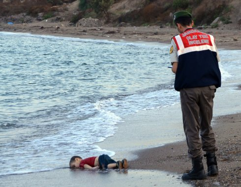 A paramilitary police officer investigates the scene before carrying the lifeless body of Aylan Kurdi, 3, after a number of refugees died and others were reported missing when boats carrying them to the Greek island of Kos capsized near the Turkish resort of Bodrum on September 2, 2015. The tides also washed up the bodies of the boy's 5-year-old brother Ghalib and their mother Rehan on Turkey's Bodrum peninsula. Their father, Abdullah, survived the tragedy.