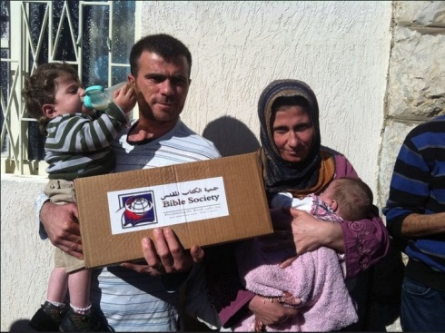 A Syrian refugee family with a Lebanon Bible Society aid package. The Bible Society provides aid for around 3,000 Syrian refugee families.
